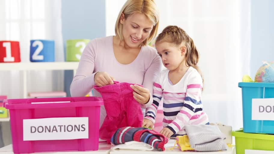 mom donating clothes with daughter