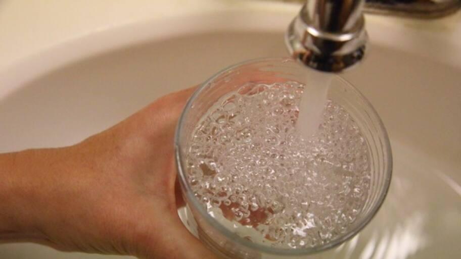 holding glass under running faucet