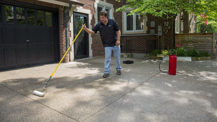 Should i seal my concrete or asphalt driveway angies list worker sealing concrete driveway solutioingenieria Image collections