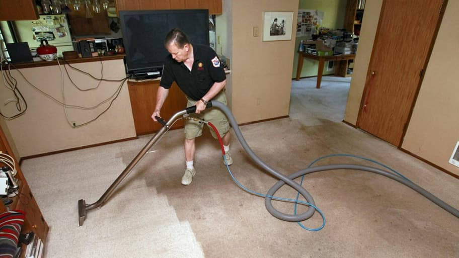 man cleaning beige carpet