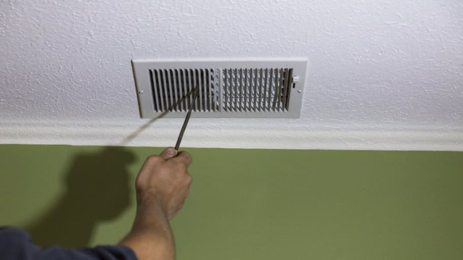 air duct cleaning worker checking vent