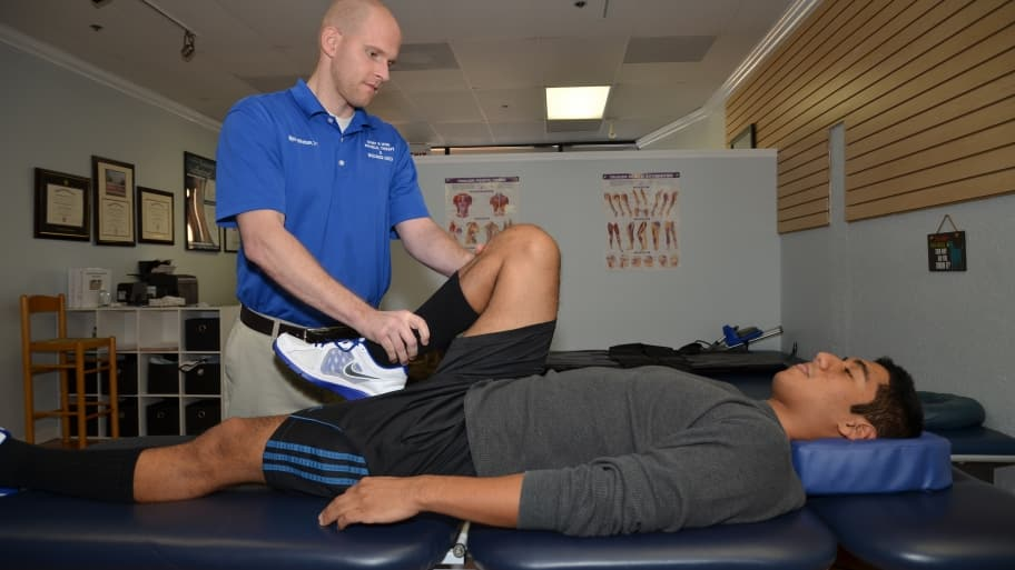 physical therapist assisting man's exercise