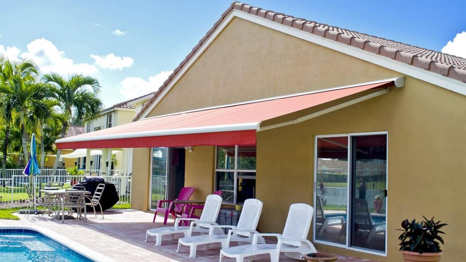 Retractable Awning Covers Poolside Patio Area With Lounging Chairs In The Backyard Of A House