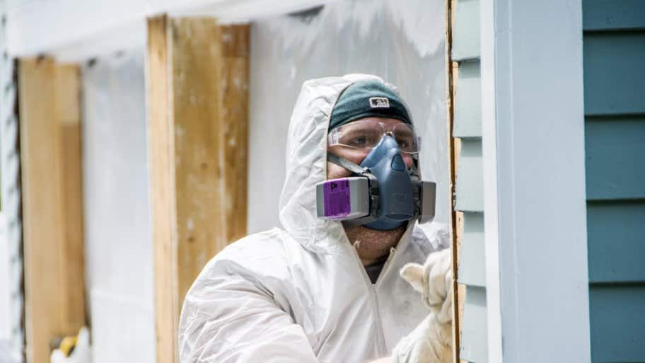 contractor in haz-mat suit scraping paint from home exterior