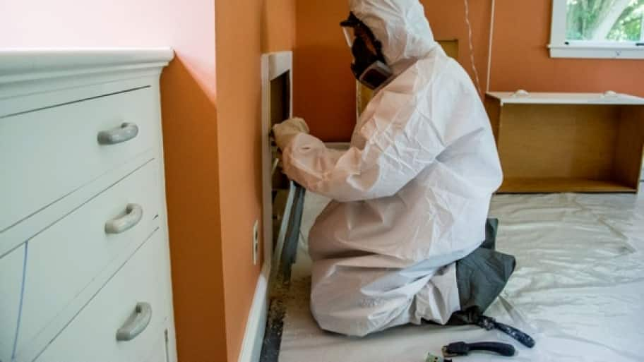 A man in a biohazard suit scraps paint off wood trim to test for lead.
