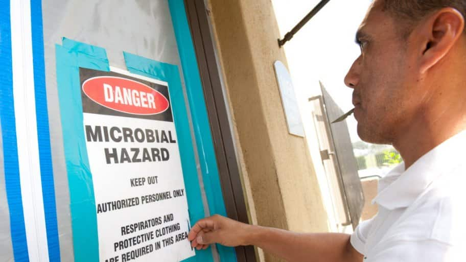 home health hazard inspector hanging a warning sign on a door