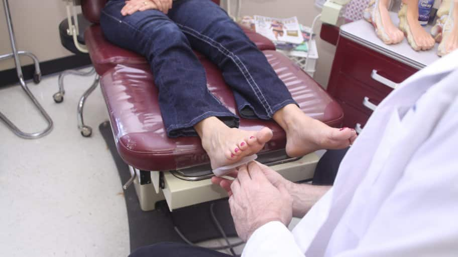 podiatrist looking at patient's feet