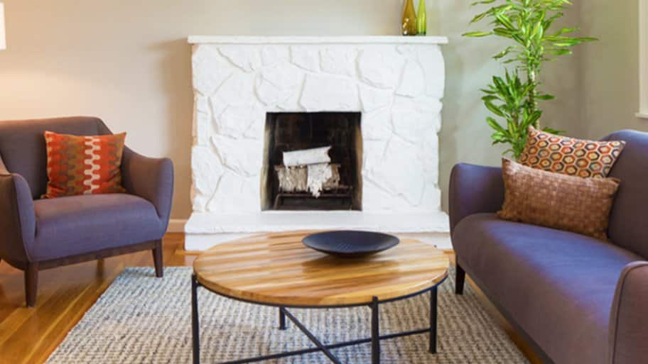 painted white stone fireplace flanked by chair and sofa