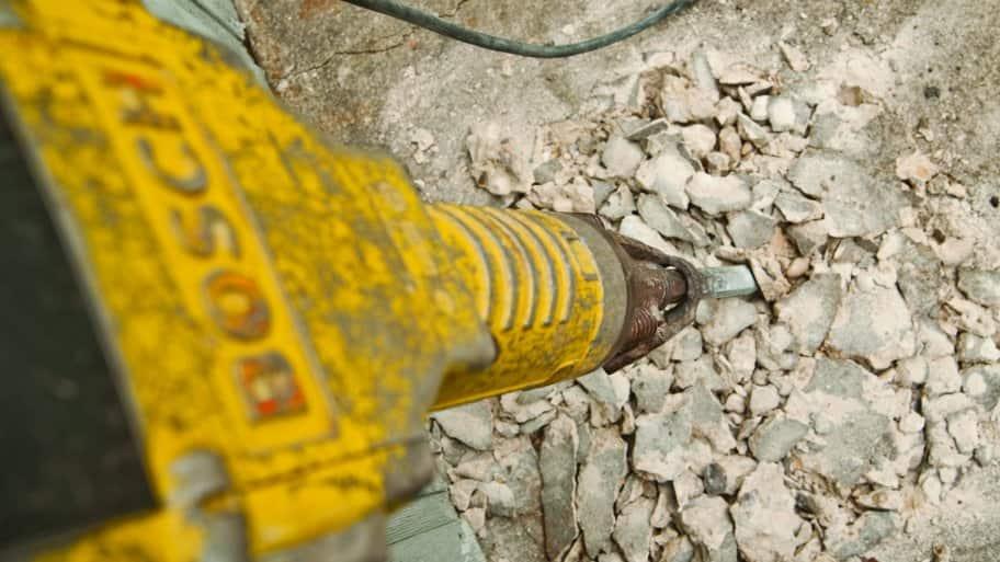 jackhammer busts up concrete foundation