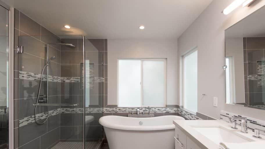 frameless shower door in remodeled gray-tone bathroom