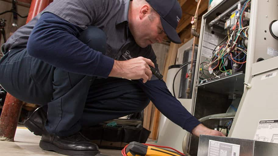 HVAC technician inspecting A/C unit