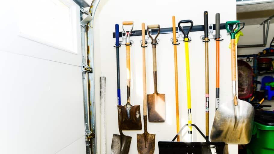 Lawn And Garden Tools Hanging On A Garage Wall