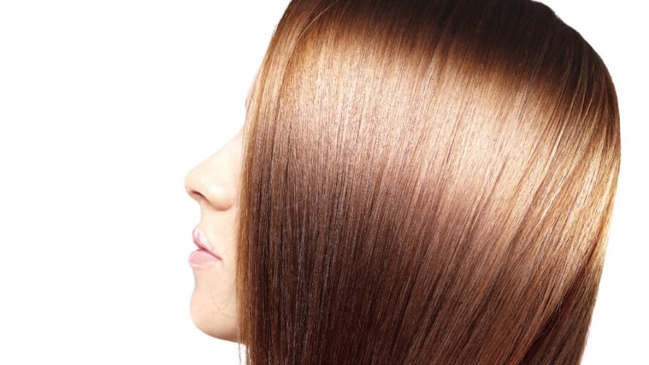 A red-headed woman after a hair gloss treatment.