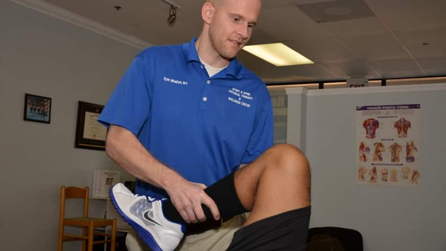 A physical therapist works with a patient
