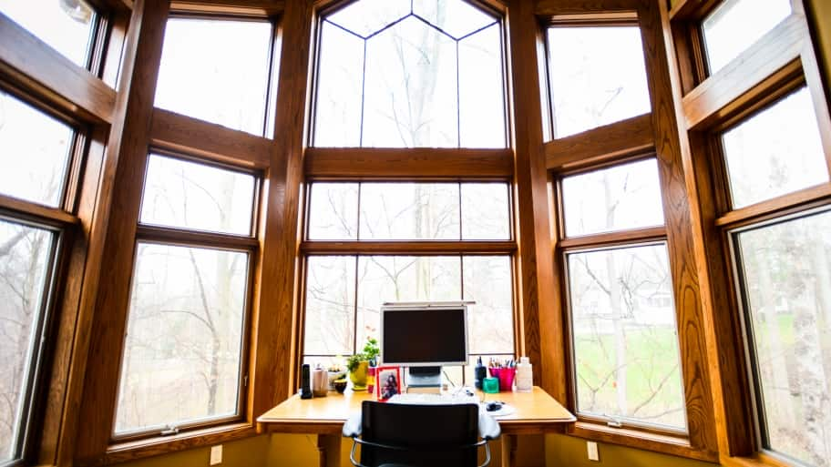 Large windows over a desk in a home office
