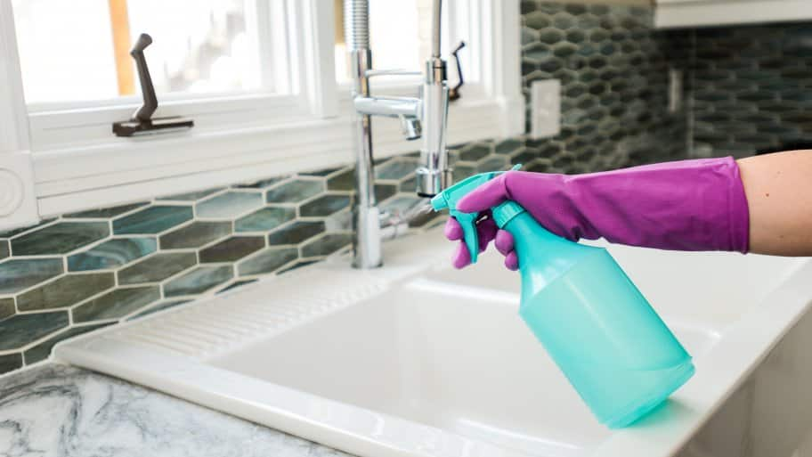 cleaner wearing rubber glove with spray bottle at sink