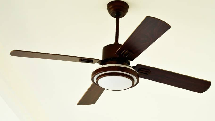 Modern ceiling fan with rubbed bronze hardware and dark wood blades on off-white ceiling