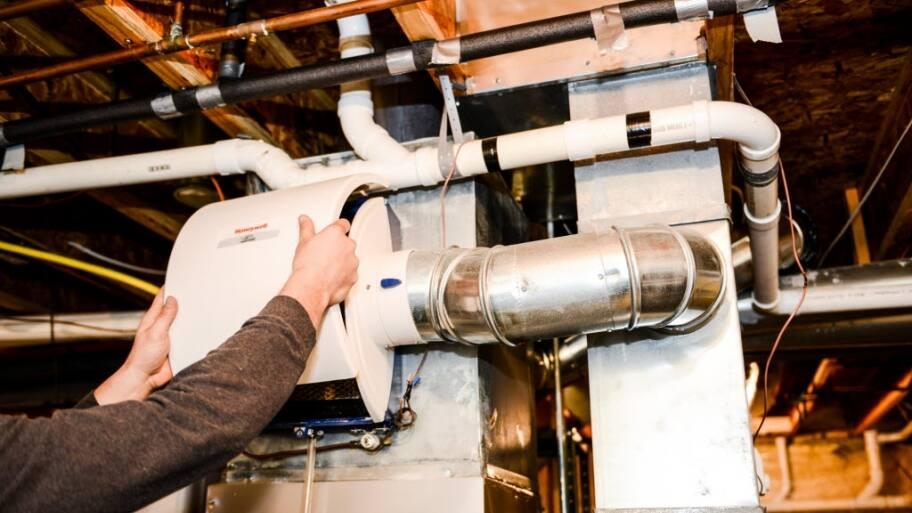HVAC technician handling an A/C humidifier