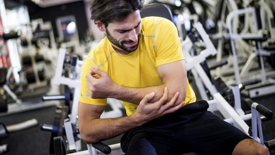 man holding injured elbow in weight room