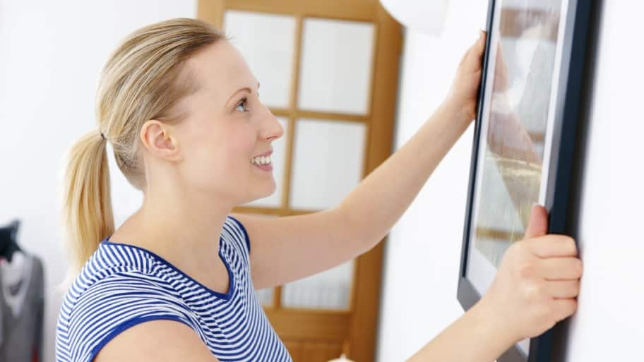 woman hanging a picture on the wall