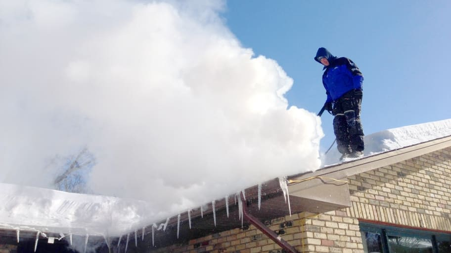 ice dam removal contractor on roof removes icicles from gutter