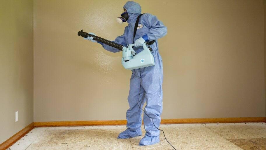 biohazard specialist in hazmat suit cleans meth home