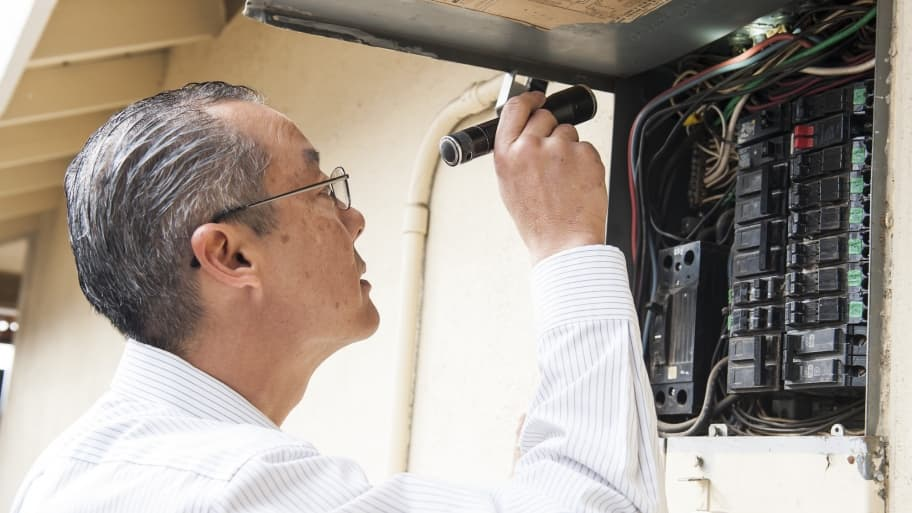 inspector examines electrical circuit breaker panel