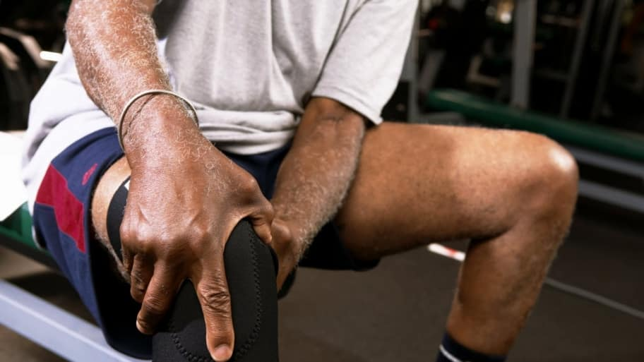 man sits on bench at fitness center massaging his knee.