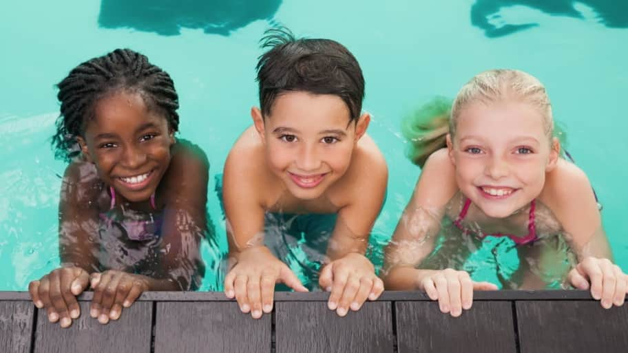 kids holding onto the side of a pool