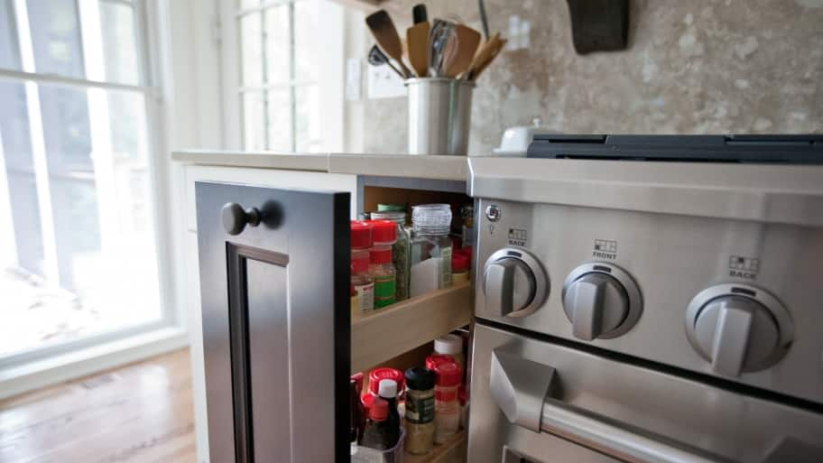 A kitchen stove with a pull-out drawer for spices