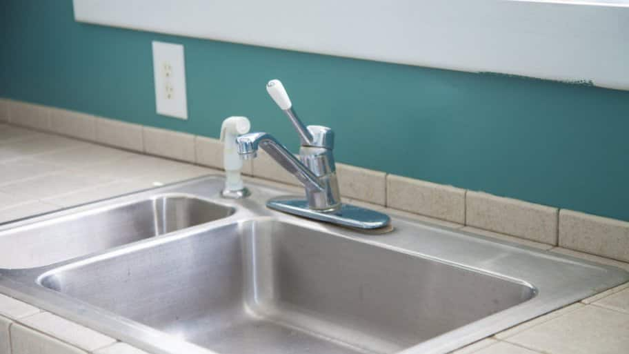 Water under the kitchen sink could be related to a leak in the faucet housing. (Photo courtesy of Katelin Kinney)