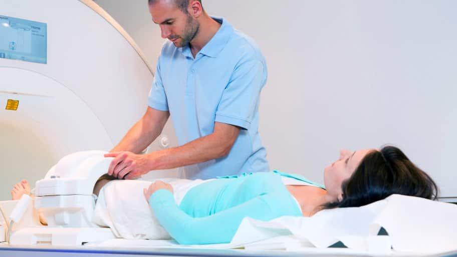 Medical technician preps woman knee for MRI