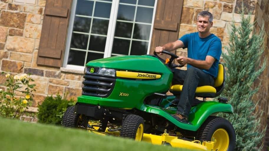 man on John Deere lawn tractor after having been freshly tuned-up with an oil change and blade sharpening