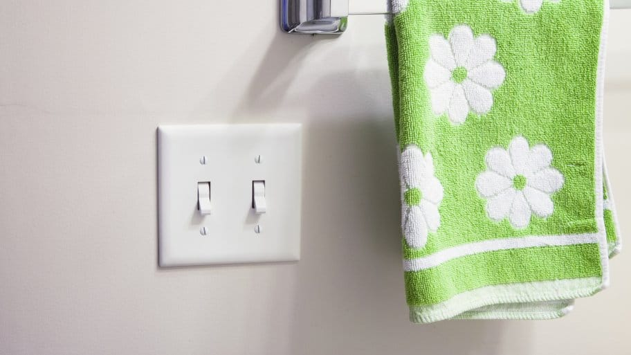 A light switch next to a towel rack