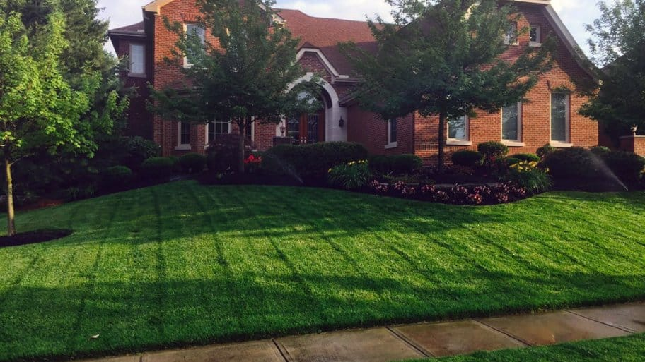 Charmant Brick Home With Lush Green Lawn Being Watered