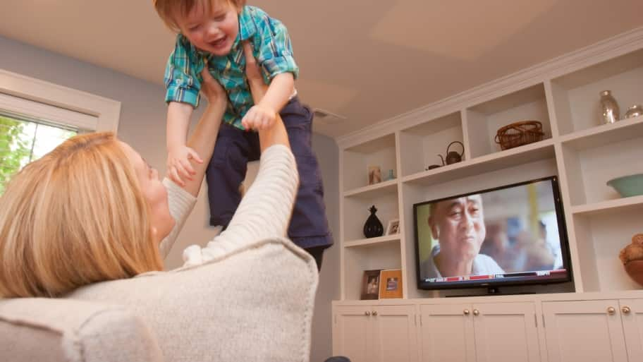 mother and child with a television in the background