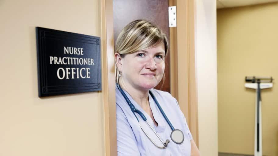A nurse practitioner standing at her office door