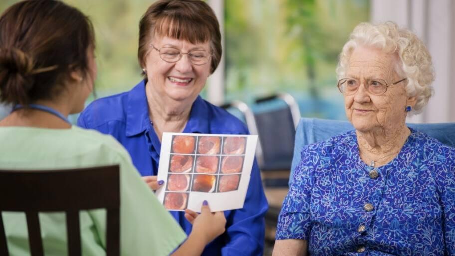 Female doctor visits elderly female patient in nursing home