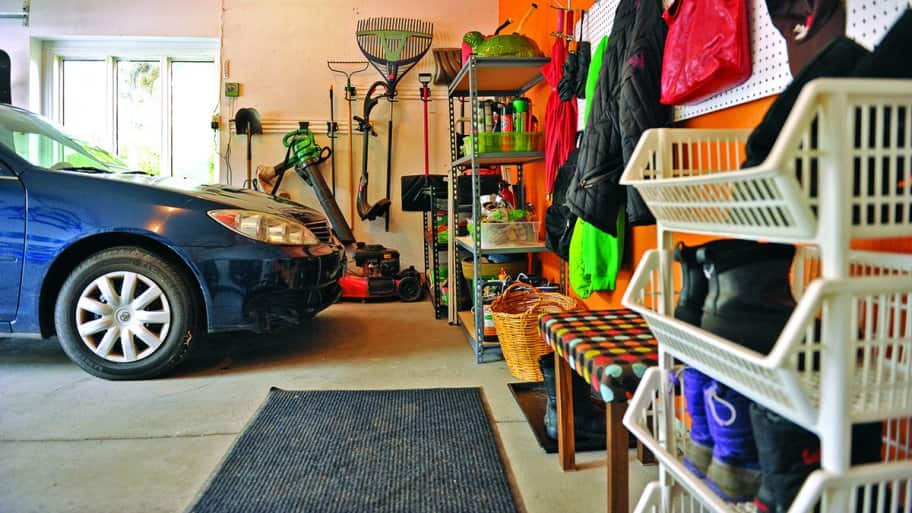 blue car in garage with lawn mower pegboard and shelves