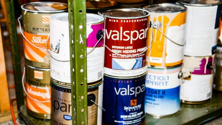 a bunch of paint cans on a rack in a basement or garage