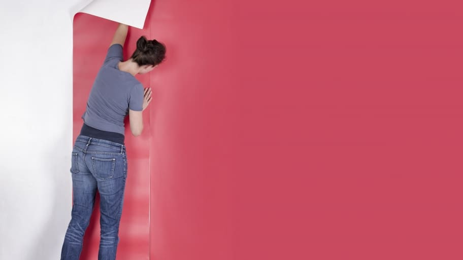 woman applying pink wallpaper