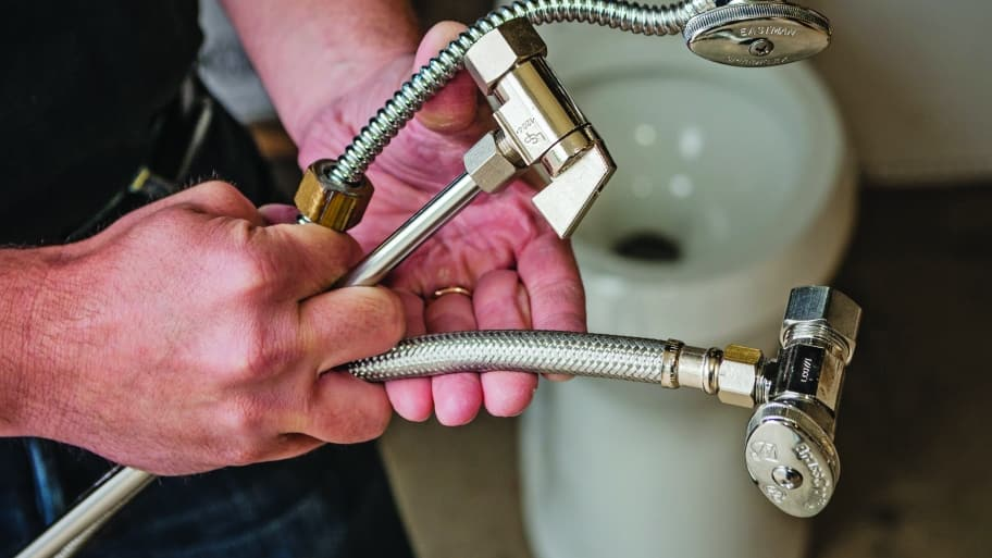 A plumber holds plumbing fixtures.