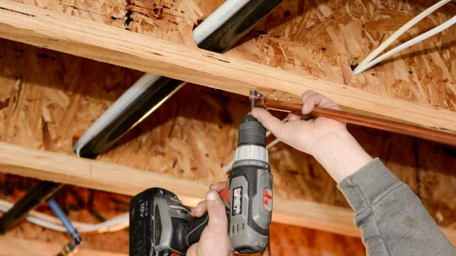 Plumber's hands installing pipe with screwdriver