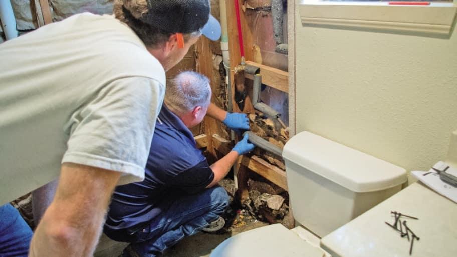 Plumbers check bathroom insulation