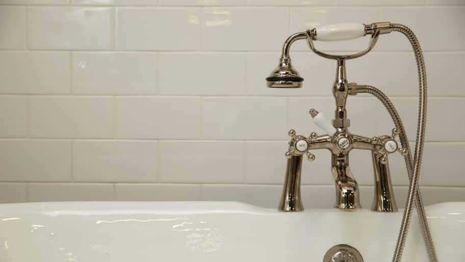bathtub with subway tile and sprayer