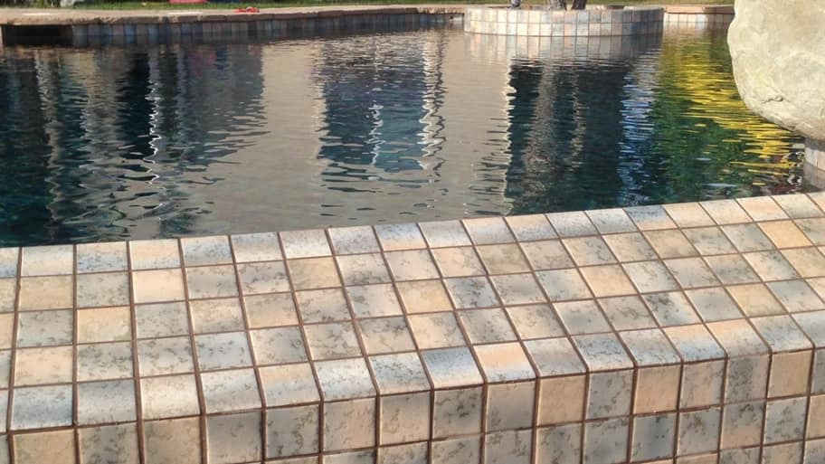 A backyard pool with new tile details and built in spa.