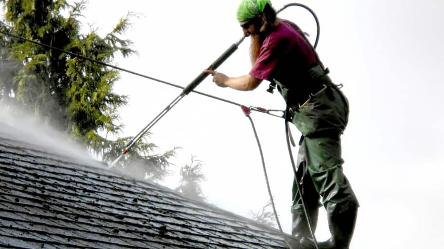 A worker pressure washes a roof that's at least 16 years old. (Photo courtesy of Angie's List member Tom Nore)
