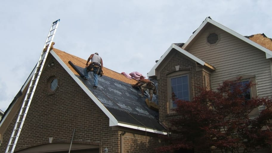 Roofers installing new asphalt shingle roof on home