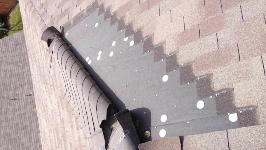 asphalt shingles torn back by wind damage