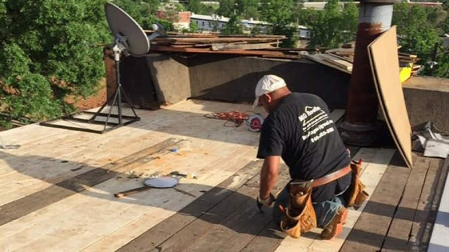 Roofer working on flat roof repair